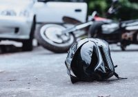 Black helmet in the foreground and wrecked motorcycle