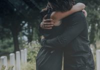A couple hugs at a funeral